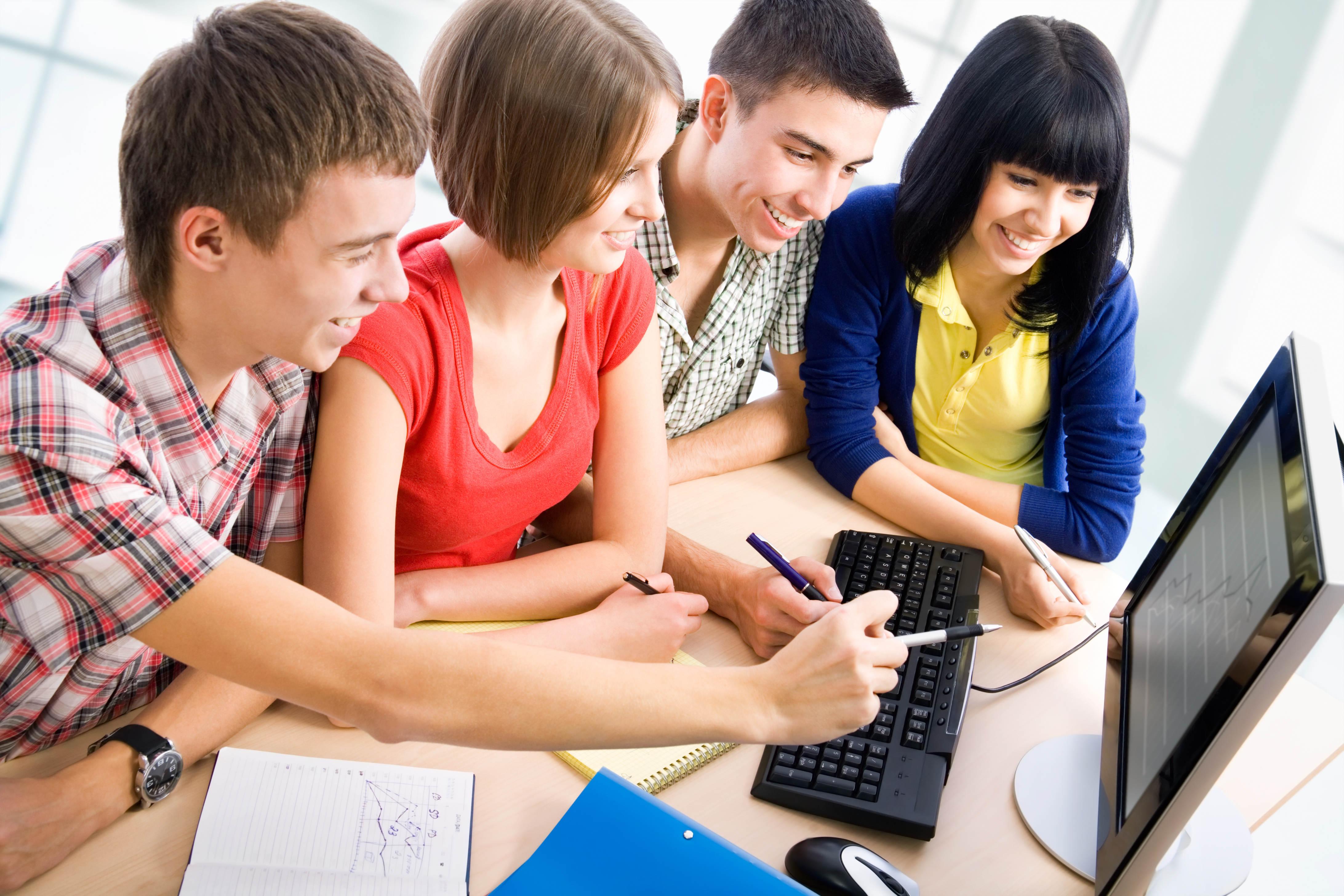 Vier Jugendliche sitzen vor einem Computer.